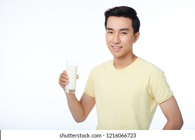 Studio portrait of handsome smiling Vietnamese man with glass of milk