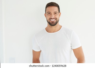 Studio portrait of handsome young man wearing white t shirt while looking at camera and smiling. Isolated on white background.