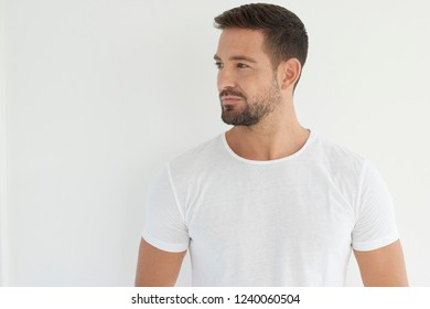 Studio portrait of handsome young man wearing white t shirt and looking away while standing at isolated white background.