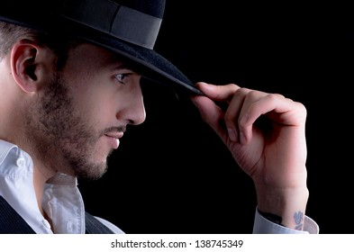 Studio portrait of a handsome young man with a hat in hand on a black background