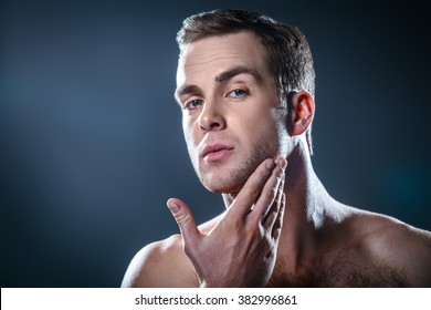 Studio portrait of handsome young man. Man with naked torso using cream after shaving
