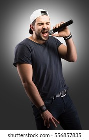 Studio portrait of a handsome young man singing to the microphone