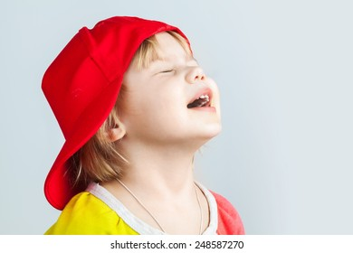 Studio portrait of happy baby girl in red baseball cap over gray wall background