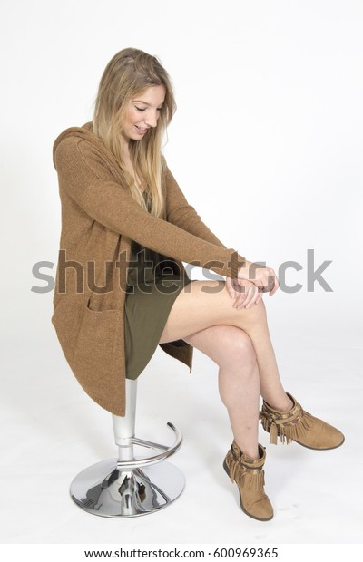 Studio portrait of happy blond woman sitting on tool on white background