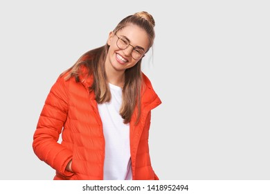 Studio portrait of happy blonde young woman smiling wide open mouth, dressing in white t-shirt and red jacket, wearing round eyewear, isolated over white background. People and emotions concept