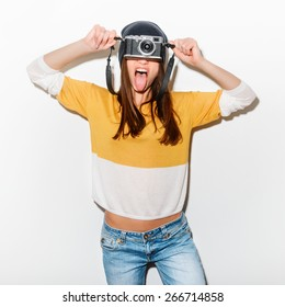 studio portrait of a happy crazy hipster girl with camera in a yellow bike and jeans on white background