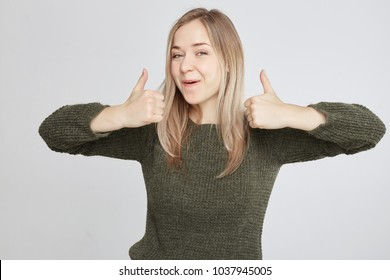 Studio portrait of happy cute young successful woman giving two thumbs up gesture in full disbelief isolated on white wall background. Positive human emotion, facial expression, body language concept