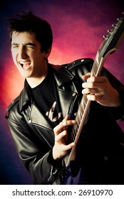 studio portrait of a happy excited young man playing guitar and screaming