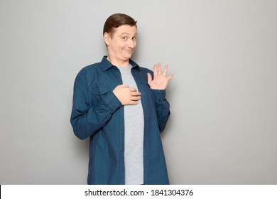 Studio portrait of happy funny blond mature man wearing blue shirt, raising hand, waving palm, saying hello or goodbye, smiling joyfully, looking friendly and goofy, standing over gray background