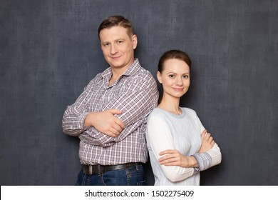 Studio portrait of happy man and woman, standing back to back, both are holding arms crossed on chest, smiling and looking kindly at camera, over gray background. Relationship and partnership concept