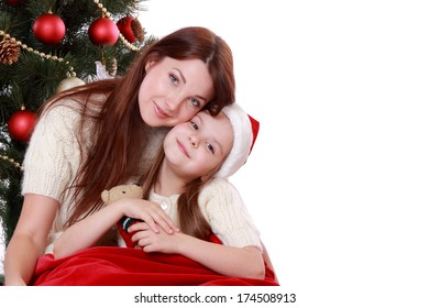 Studio portrait of happy mother and daughter over christmas tree on Holiday theme isolated on white/happy mother and daughter over christmas tree