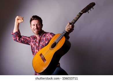 studio portrait of a happy musician or singer with classic guitar