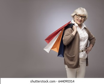 Studio portrait of happy senior woman with shopping bags