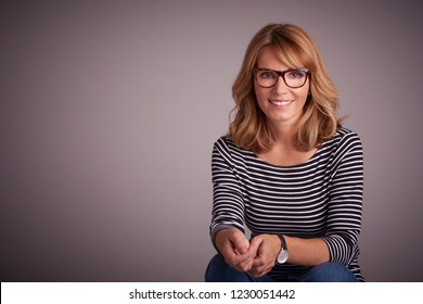 Studio portrait of happy woman sitting against at isolated grey background while looking at camera and laughing.