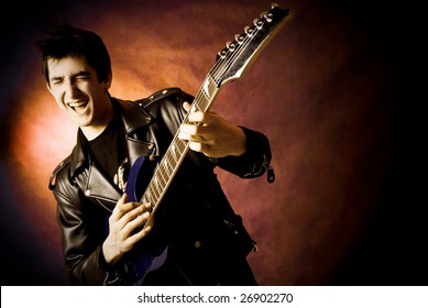 studio portrait of a happy young excited man playing a guitar