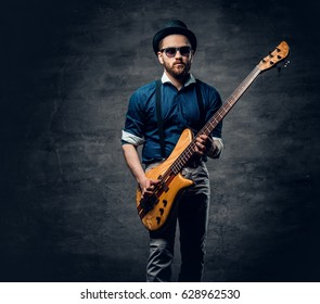 Studio portrait of the hipster bass player dressed in cylinder hat.