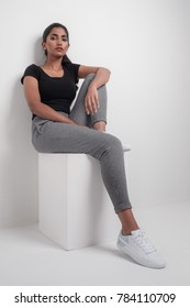 Studio portrait of indian model sitting casually on a box with a nonchalant expression