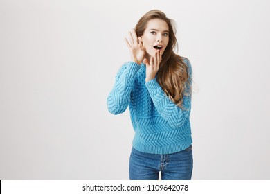 Studio portrait of intrigued european woman who likes to gossip, bending towards camera with hands near ear and opened mouth, being shocked with what she heard while eavesdropping or listening rumor