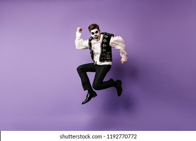 Studio portrait of jumping laughing man in halloween costume. Indoor photo of excited guy with mexican makeup dancing on purple background.
