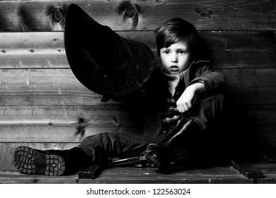 studio portrait of little cowboy holding his hat in hand