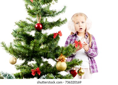 Studio portrait of little girl decorating Christmas tree