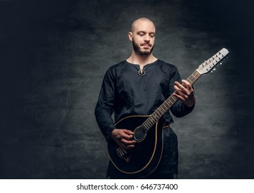 Studio portrait of a man in traditional Celtic clothes playing on mandolin over grey vignette background.