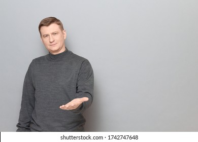 Studio portrait of man wearing jumper, smiling and stretching hand to you, expressing cordiality and hospitality, feeling respect and gratitude, standing over gray background, copy space on right