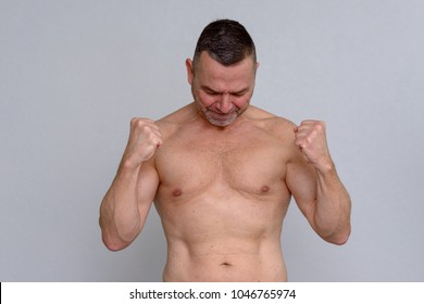 A studio portrait of a mature man naked from the waist up looking triumphant as he clenches both fists.