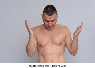A studio portrait of a mature man naked from the waist up looking frustrated as he throws his hand in the air.