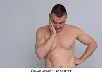 A studio portrait of a mature man naked from the waist up looking fed up and depressed.