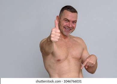 A studio portrait of a mature man naked from the waist up looking happy as he gives a thumbs up sign to the camera.