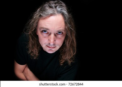 Studio portrait of mid aged man with long hair and amazing eyes on dark background