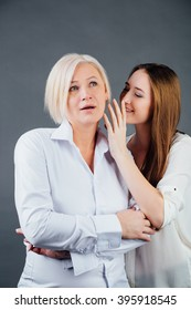 Studio portrait of mother and adult daughter. Daughter shares the secret to her mother's ear, in white shirt on a gray background.