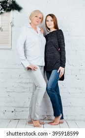 Studio portrait of mother and adult daughter. Embraced barefoot. Full length. Against the background of a white brick wall
