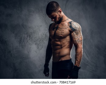 Studio portrait of muscular, shirtless, tattooed male over grey background.
