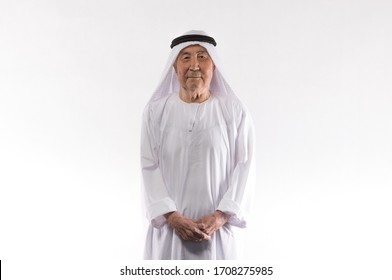 studio portrait of an old Arab man in white clothes on a white background
