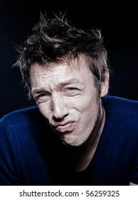 studio portrait on black background of a funny expressive caucasian man puckering annoye