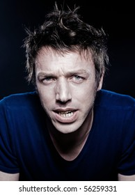 studio portrait on black background of a funny expressive caucasian man frowning pensiv