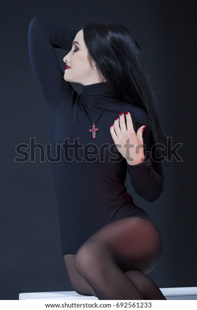 Studio Portrait of Passionate Sexy Caucasian Brunette Woman in Black Body Suit Posing on White Box Against Black Background. Vertical Composition