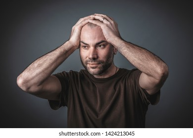 Studio portrait of pensive man with his hands holding his head. Casual clothes.