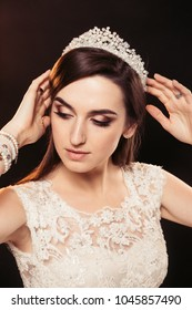 Studio Portrait of Pretty Brunette Bride with Hairstyle, Sensual Makeup and Diadem on Her Head on Black Background