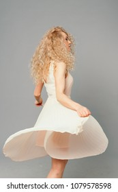 Studio portrait of a pretty curly blonde woman, wearing light dress, smiling and looking at the camera, against plain studio background
