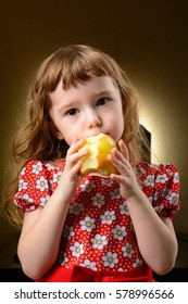 Studio portrait of a pretty little girl with an apple