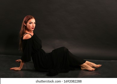 Studio portrait of pretty woman in black dress on dark background