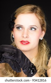 Studio portrait of pretty young woman with red lipstick and long blond hair. Wearing a black dress and gloves. Isolated on black background.