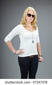 Studio portrait of pretty young woman wearing sunglasses and white shirt isolated on grey background