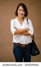 Studio portrait of a professional looking middle aged Chinese Asian woman in a smart casual (white shirt and jeans) and a sling bag. She is casual, relaxed, happy and smiling; her arms are crossed.