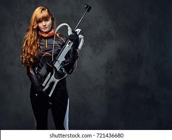 Studio portrait of a redhead female Biathlon champion holds a gun over grey background.