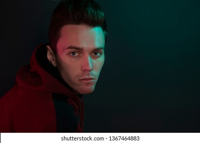 Studio portrait of a sad guy in a hoodie on black background. Close-up, using green and red back lights.
