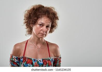 Studio portrait of a sad mature woman  on gray background
